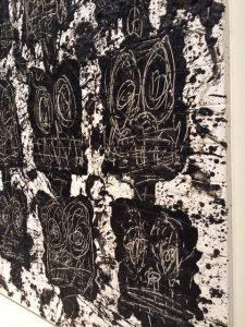 """A gallery is covered with the faces of the """"Anxious Audience"""" pieces made with wax on black soap backed by ceramic tiles."""