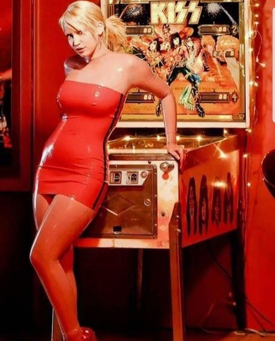 sexy girl playing pinball in red dress