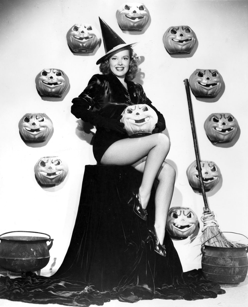 pretty witch with pumpkin faces on wall