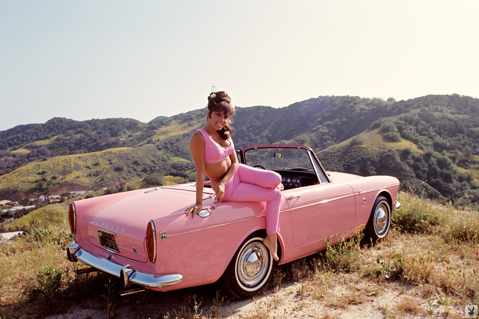 pink convertible on mountaintop with pinup girl in pink