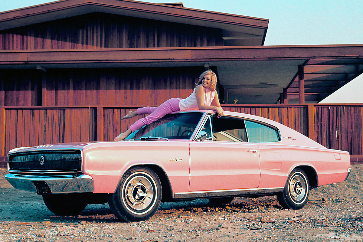 pinup girl on top of classic pink car auto