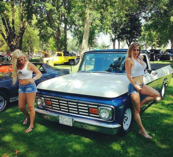 two babes with matching tank tops with classic truck