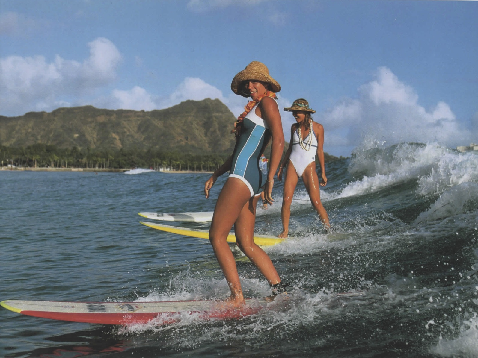 two cute surfer girls cruising on a wave together