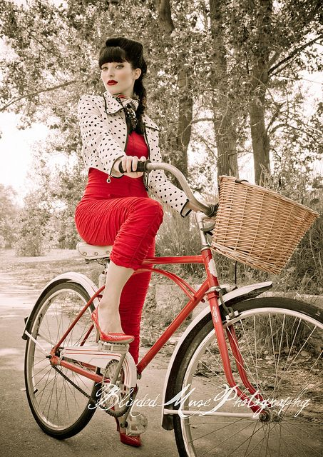 brunette pinup girl in red on cute red bike with basket