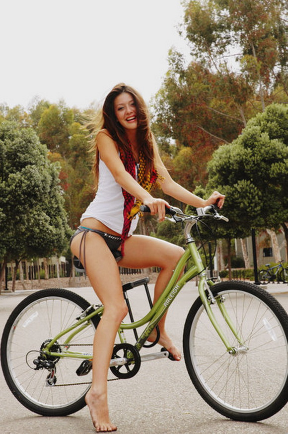 good looking brown haired girl laughing on a bicycle