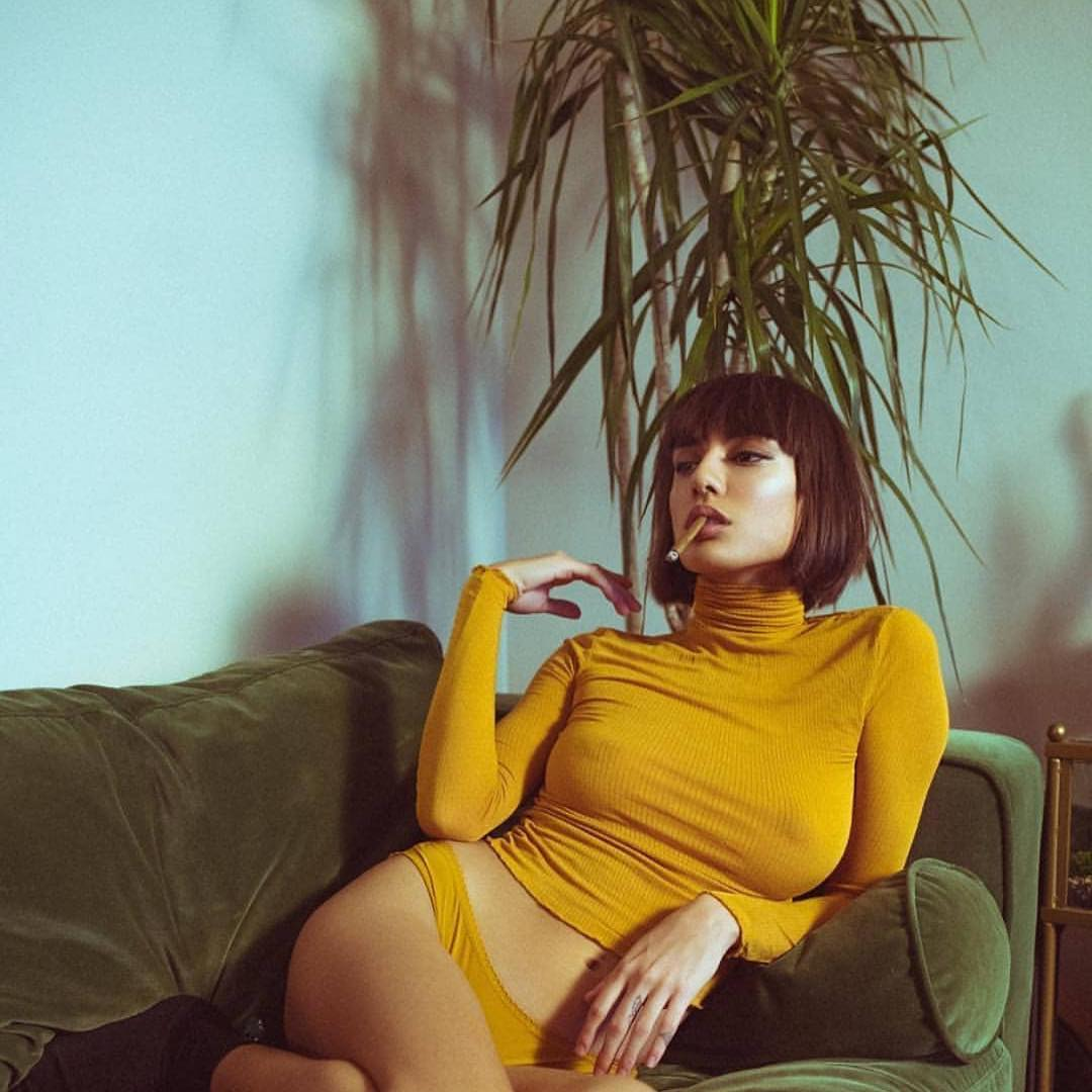 stylish brunette model with blunt in yellow looking hot