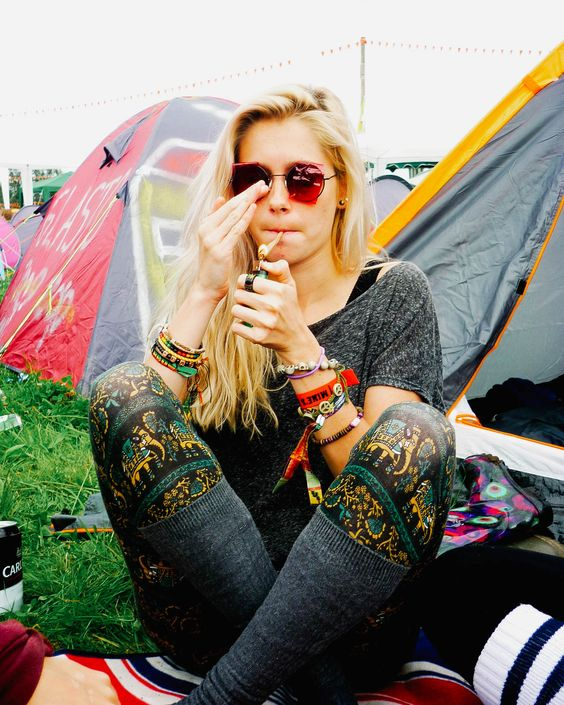 blonde hippie girl at festival getting high with joint blunt