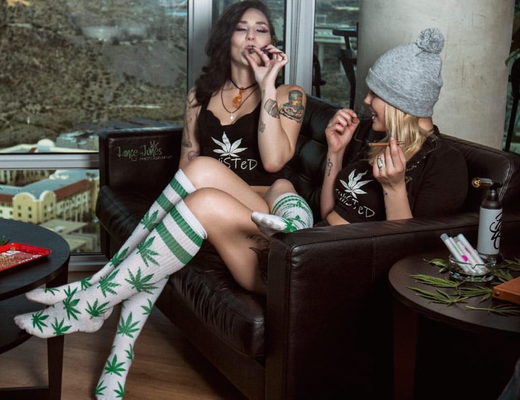 two cannabis babes getting high on a couch