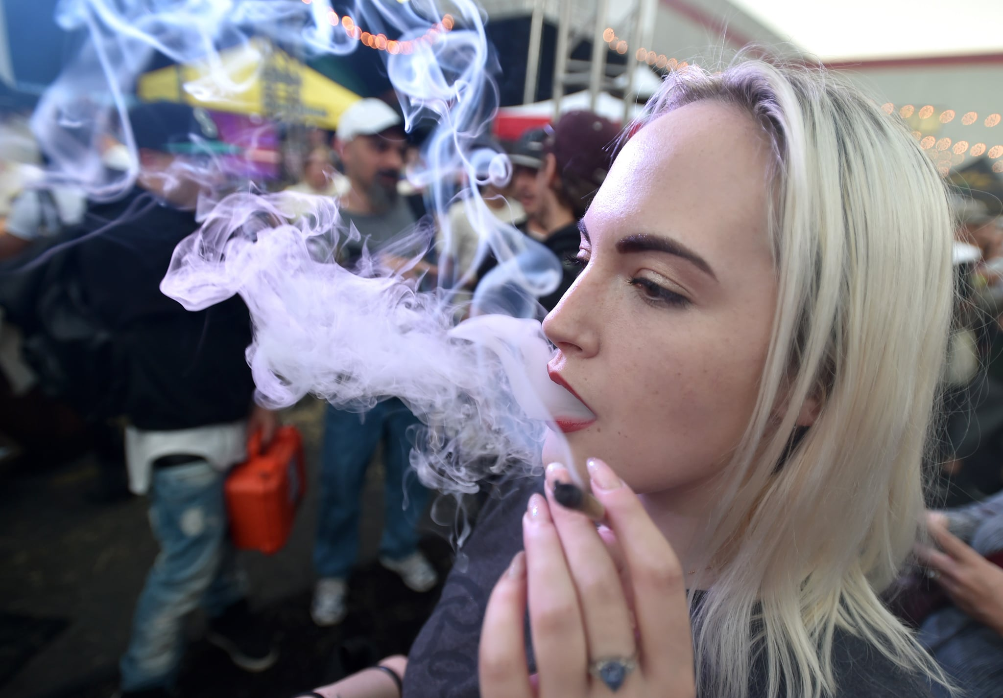 hot blonde girl at hemp festival getting blazed
