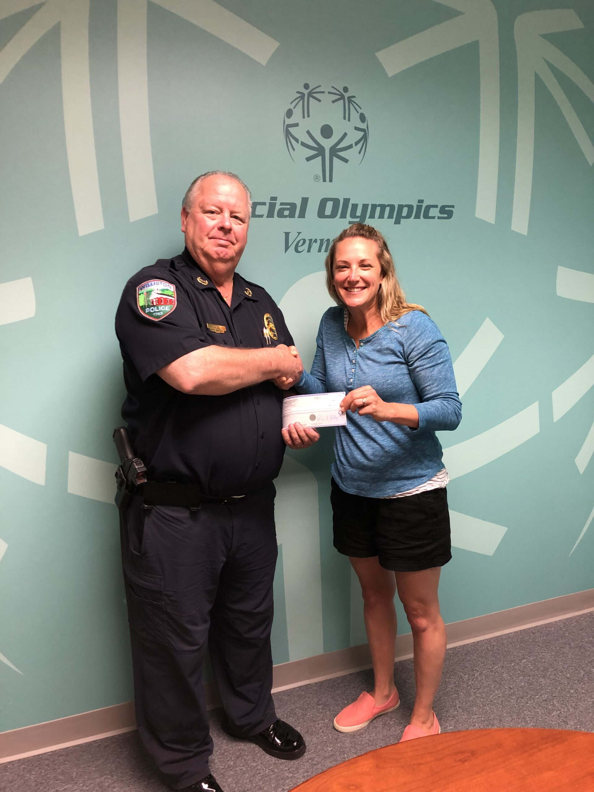 Police chief presenting donation check to woman