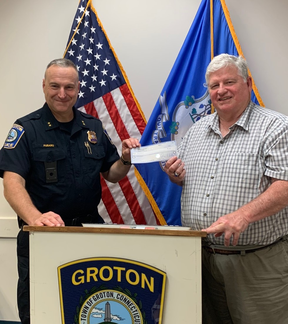 A chief of police in uniform presenting a check to a man in front of American flag