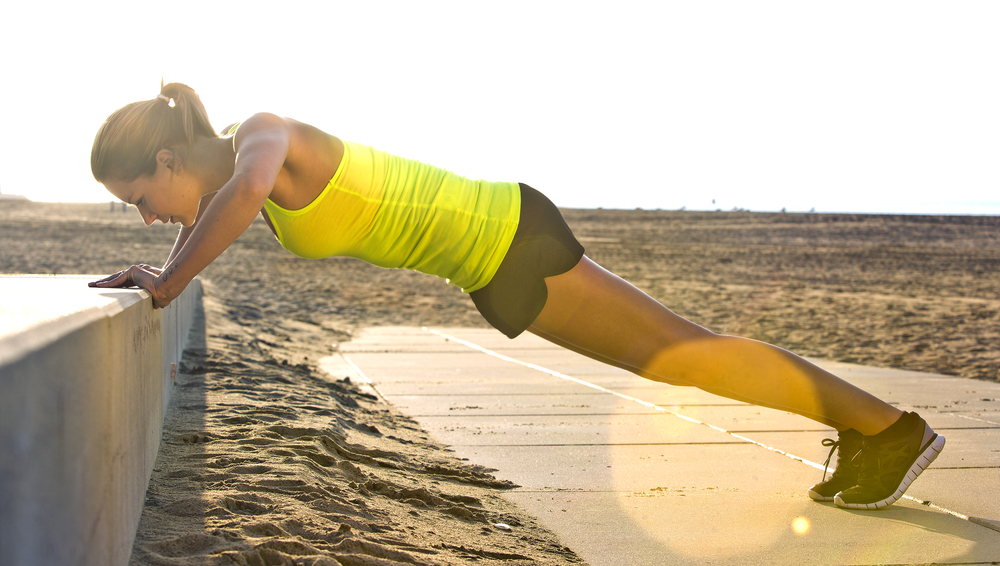 woman exercising while traveling, push ups