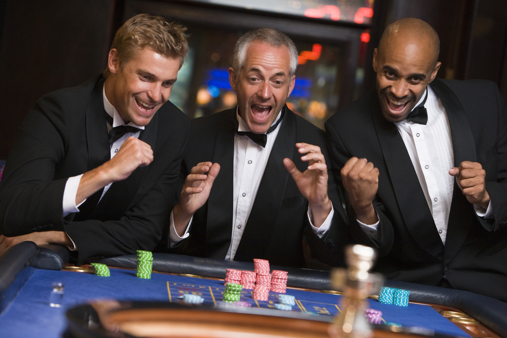 middle-aged men celebrating at a casino