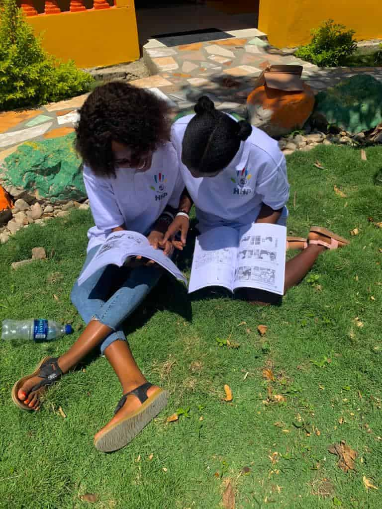 Two empowered students read books on the lawn of the school