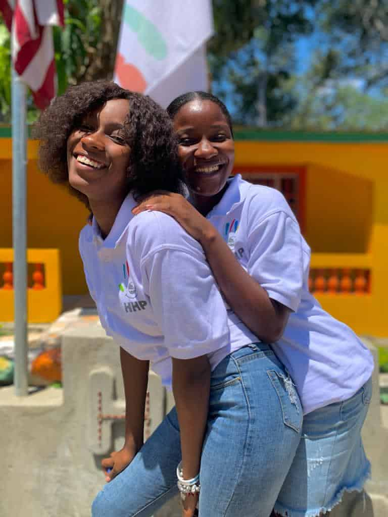 Two empowered students pose in front of the new school flags