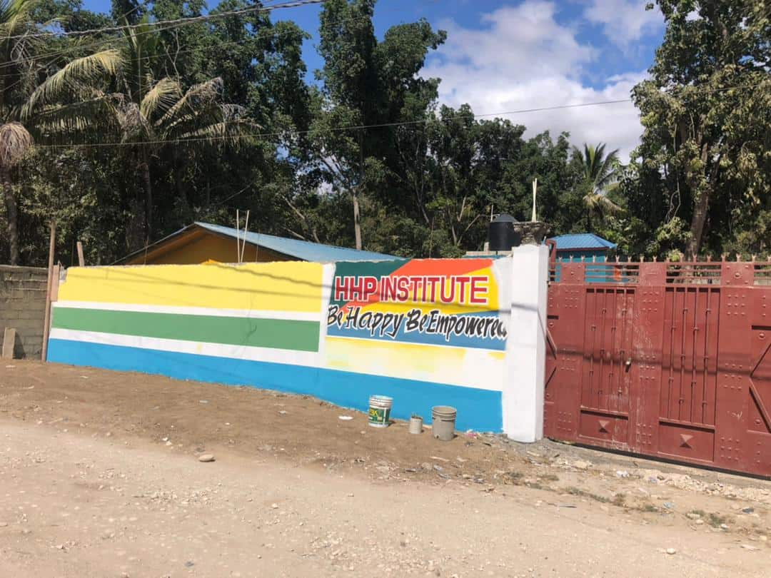 A close up of our gated school with a wall painted in our brand colors