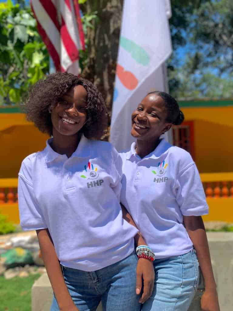 Two empowered students stand in front of school flags