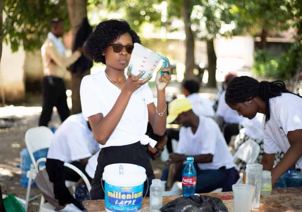 One student holds a liquid measurer used to make soap while outdoors in Hinche