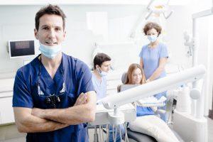 Dentist and dental hygienists prepare patient for laser dentistry procedure