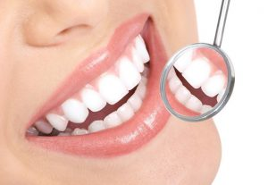 A bright, white smile reflecting in a dental mirror