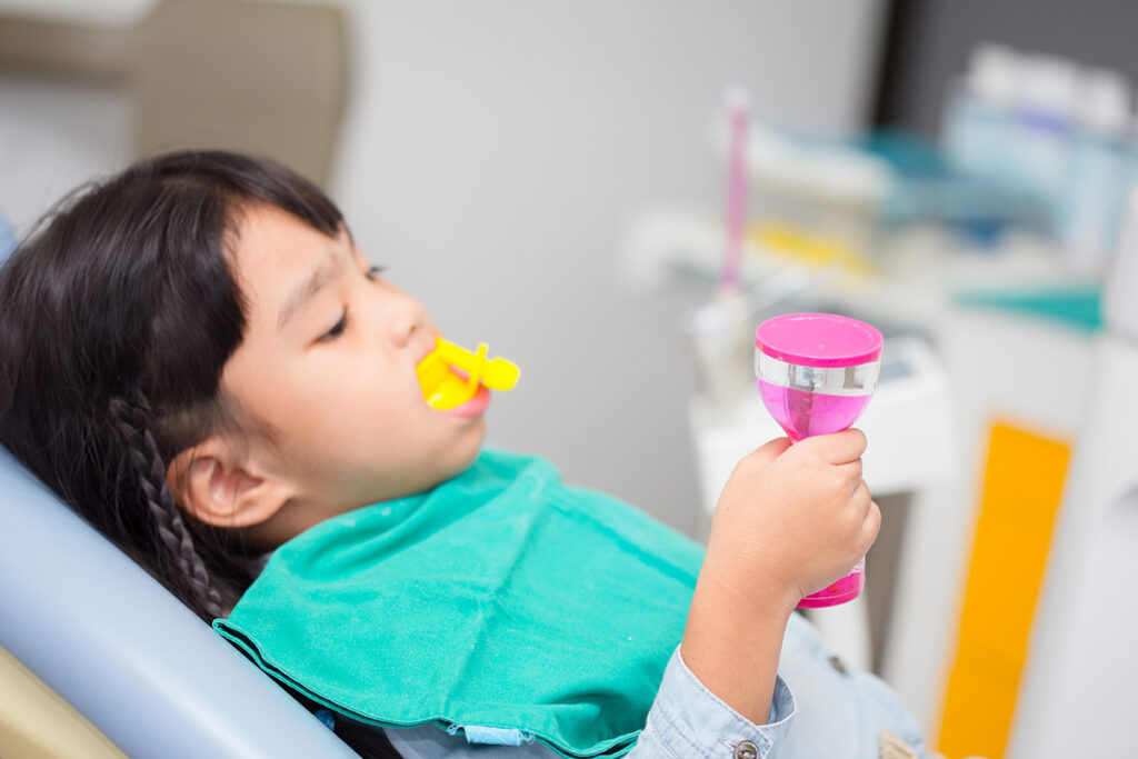 Little girl receiving a fluoride treatment at Cobblestone Park Family Dental in Oklahoma City