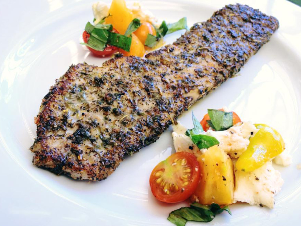 Rockfish fillet, blackened. Served with heirloom tomato and mozzarella salad. Photo CC-BY-4.0: Ben Young Landis.