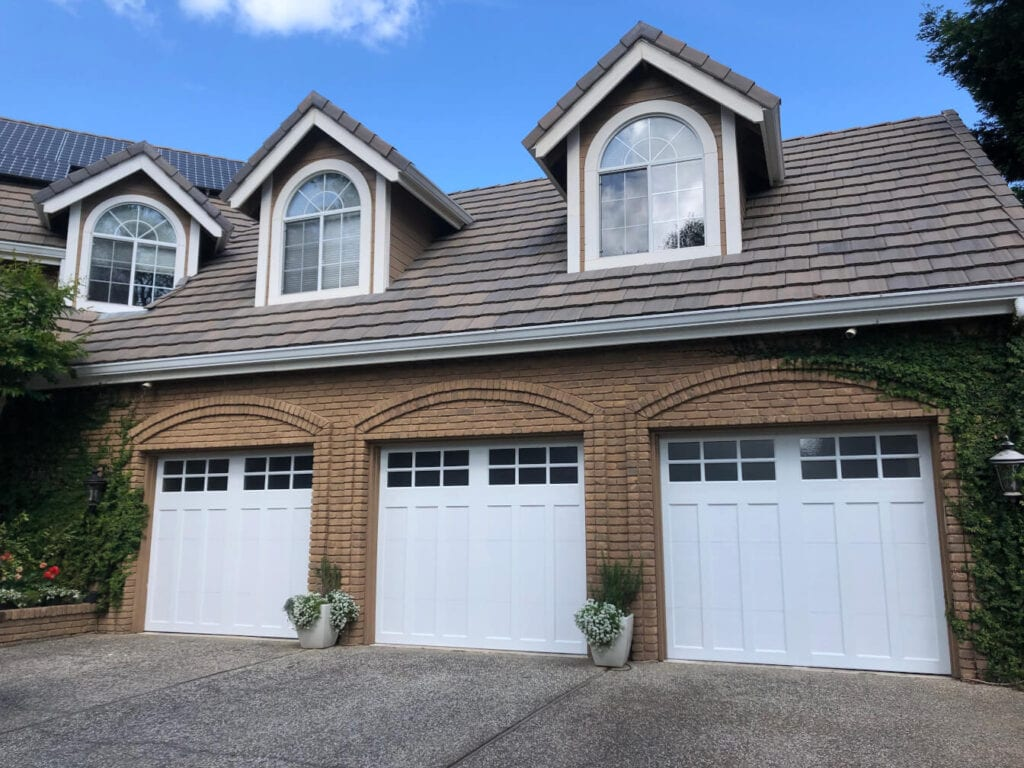 picture of a garage with three new single garage doors installed.