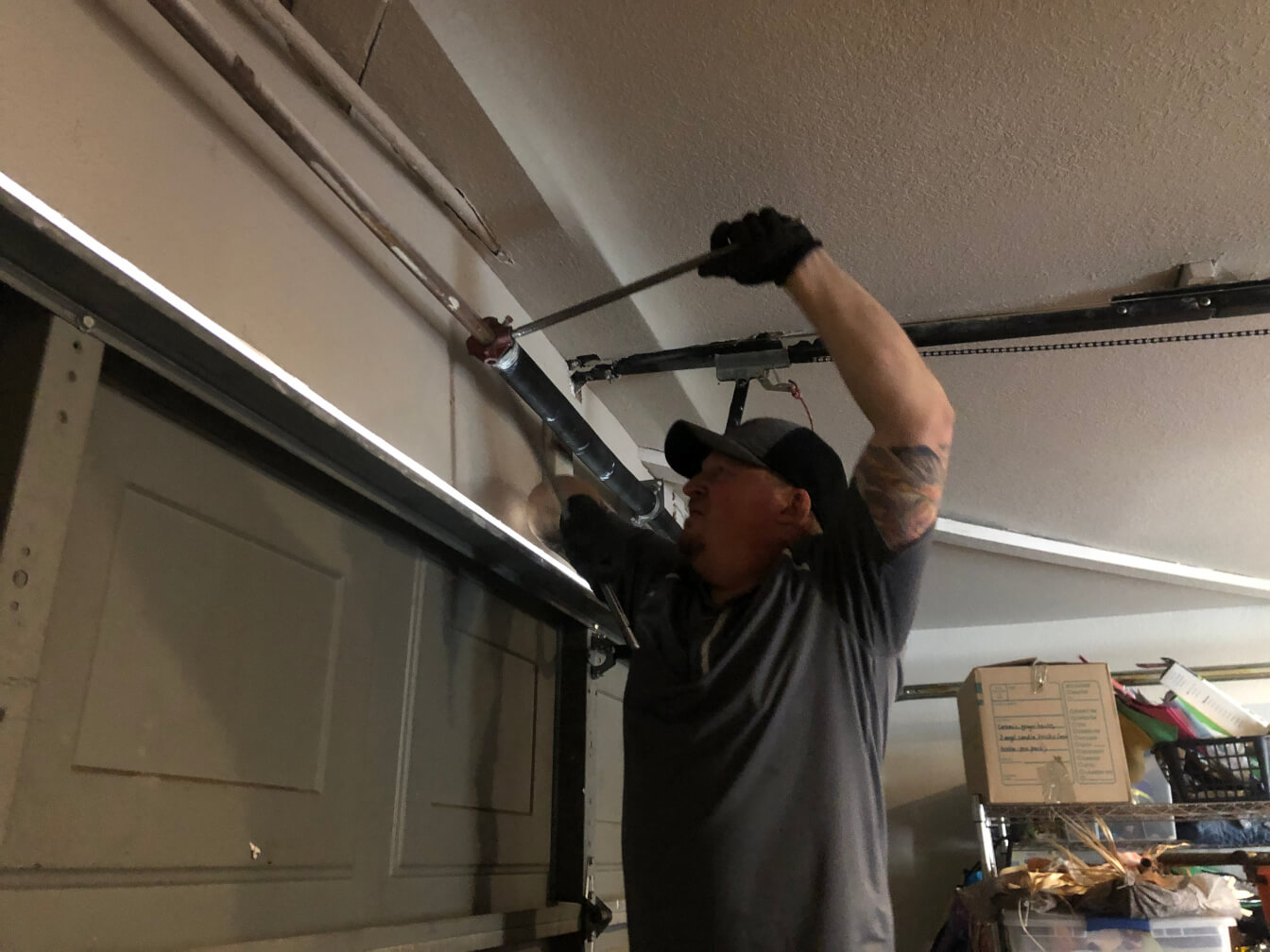 Image of a service technician installing a new garage spring.