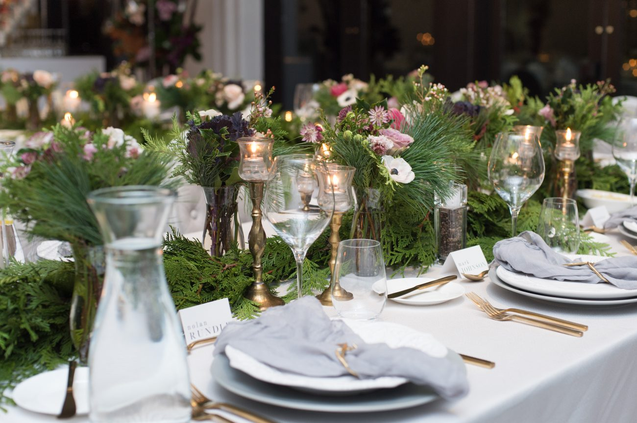holiday party centrepieces with pines and gold accents