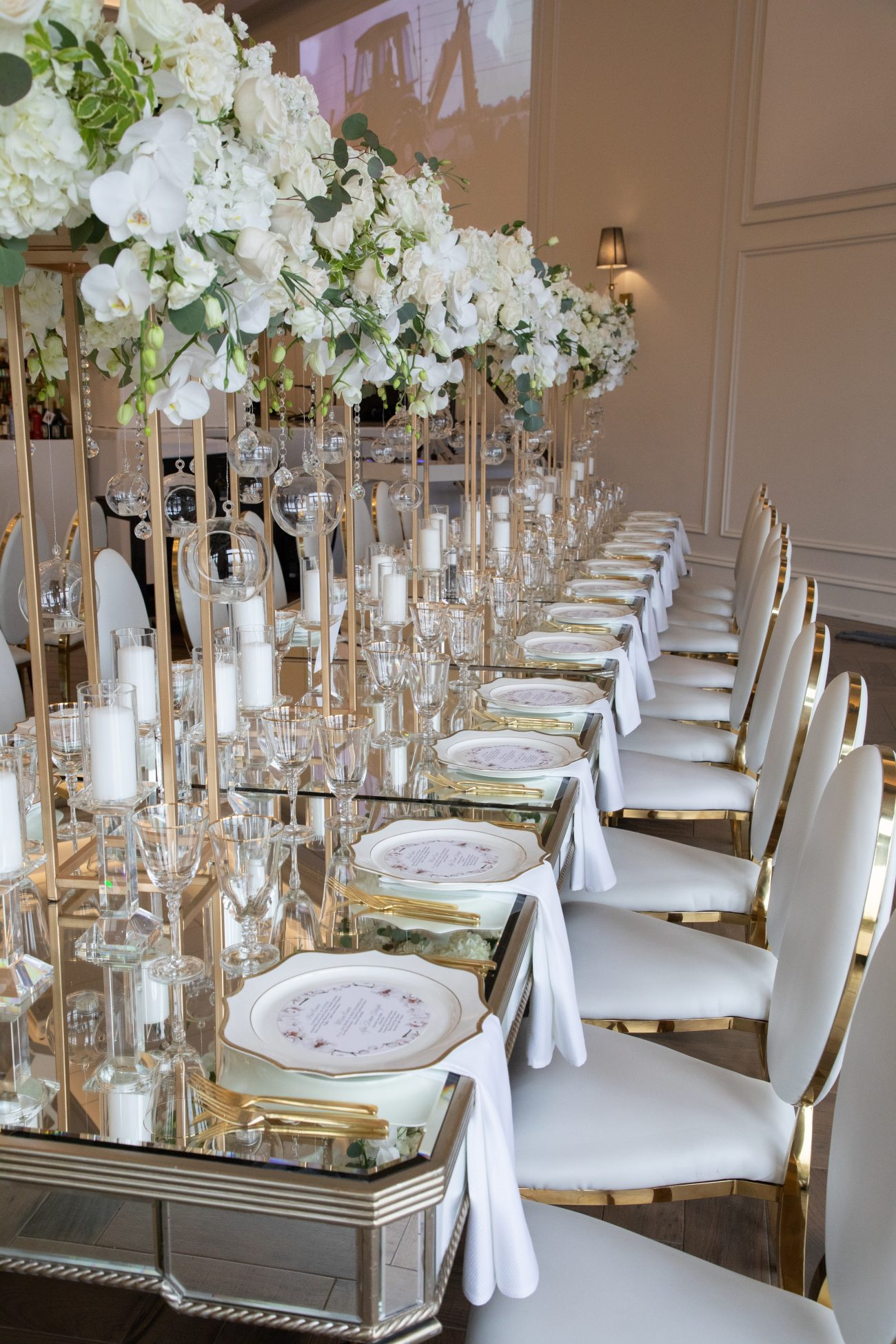 Elegant white and gold table setting with tall centrepieces