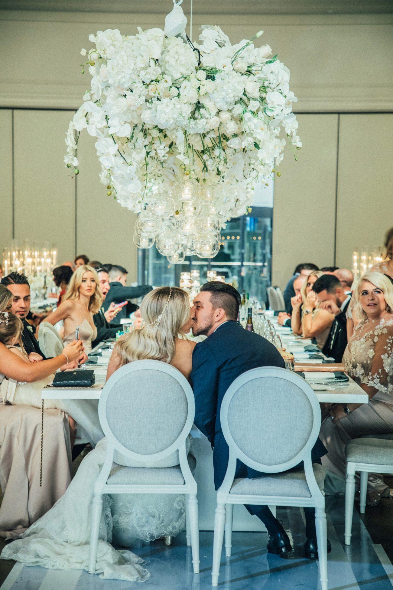 newlyweds kissing at head table