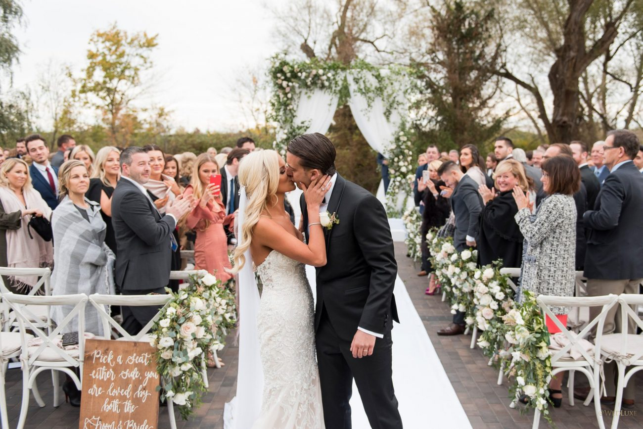 Beautiful newlyweds kissing in outdoor ceremony