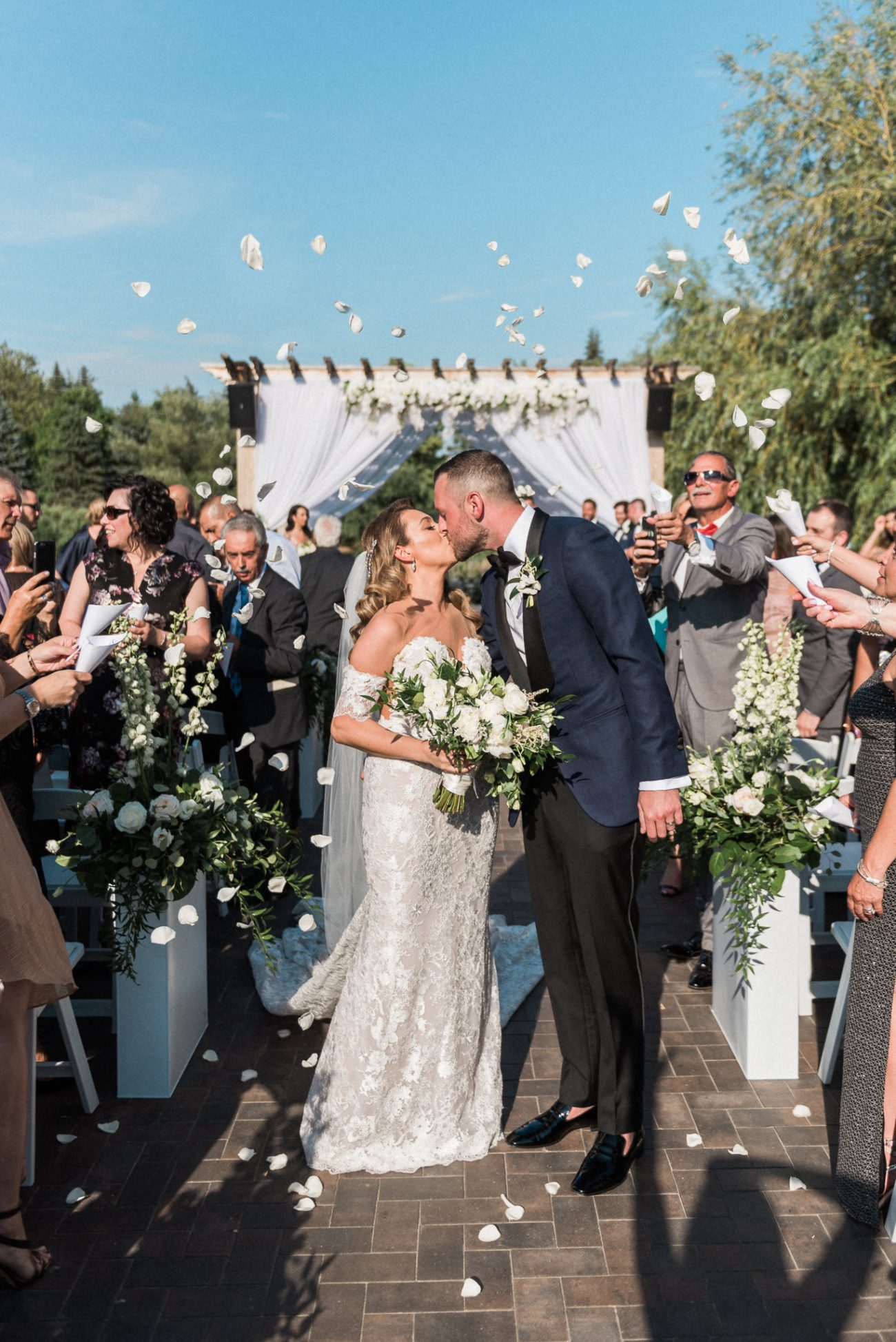 Happy newlyweds kissing after outdoor wedding ceremony