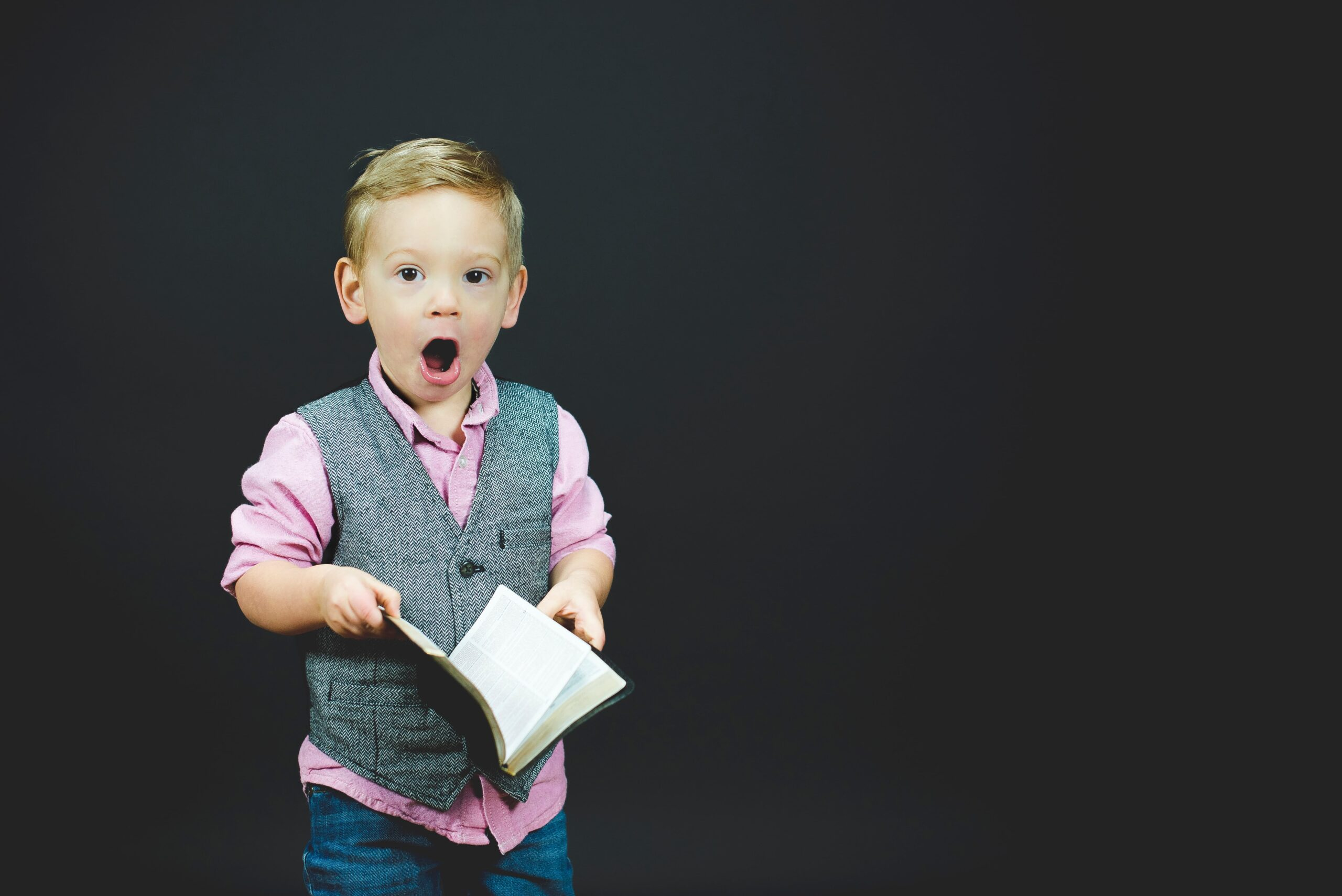 small boy holding book