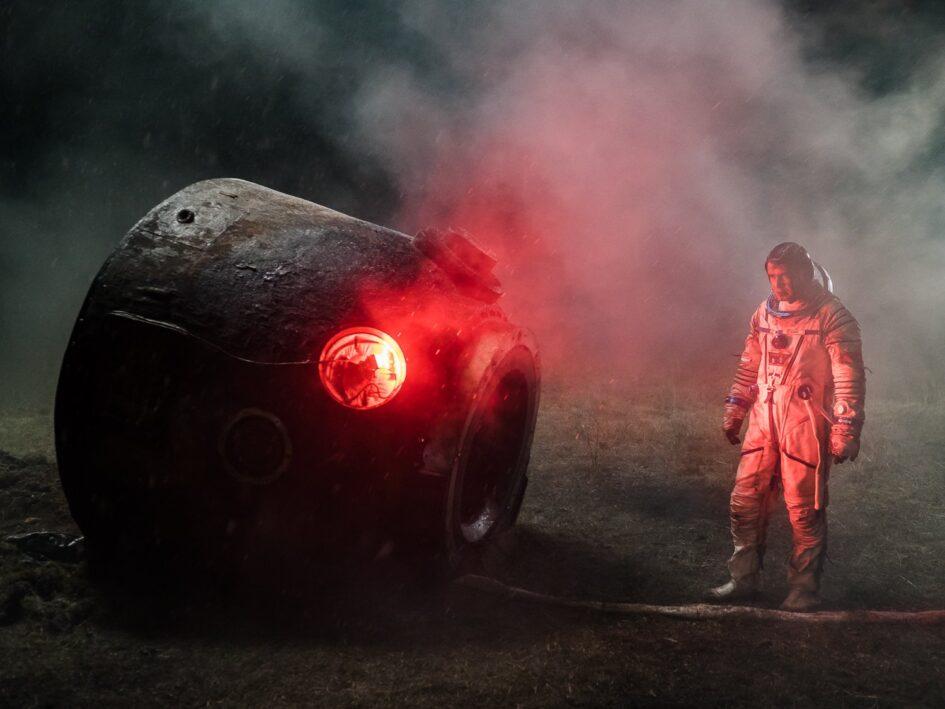 Russian cosmonaut standing beside smoking space capsule