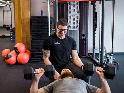 Personal trainer Josh working on dumbell press with client.