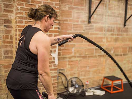 Client using battle ropes during open gym time