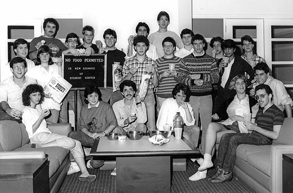 The 1987 Thresher staff demonstrate their obedience to posted instructions in the new Student Center lounges. Editor Lisa Gray '88 is seated in the front row, behind a bottle of contraband soda.