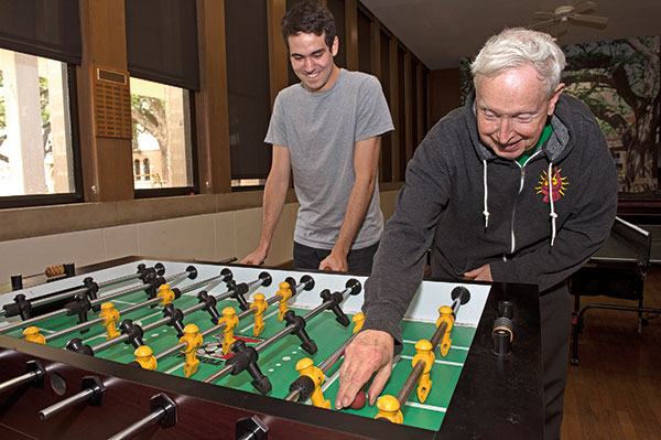 "Glibert ""Doc C"" Cuthbertson plays foosball with a student in the Will Rice game room."