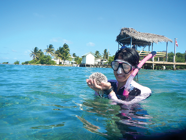 Junior Stephanie Zhao admires a West Indian sea egg, a species of sea urchin that inhabits seagrass beds near Middle Caye, an island inside Glover's Reef Atoll. Photo courtesy of Scott Solomon
