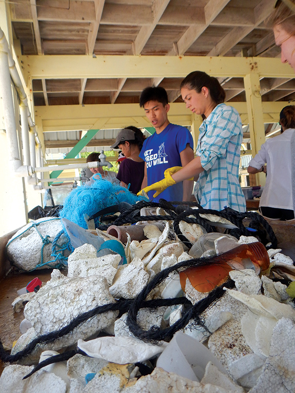 Students measure the amount of trash that washes up on the shore of Middle Caye. Photo Courtesy of Scott Solomon