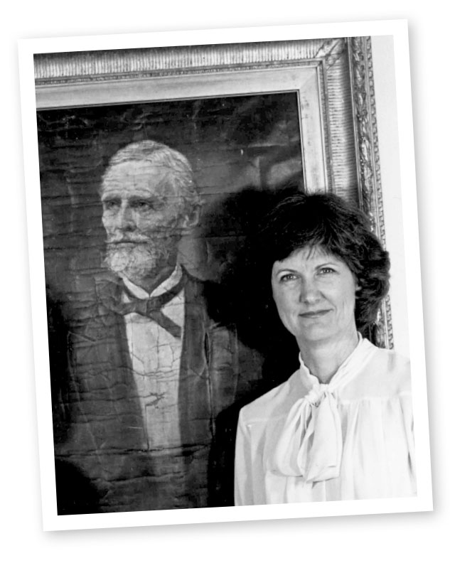 Lynda Crist poses with a painting of Jefferson Davis.