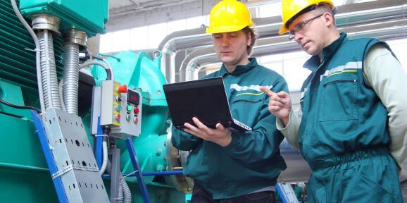 Workers checking efficiency in manufacturing using a tablet app.