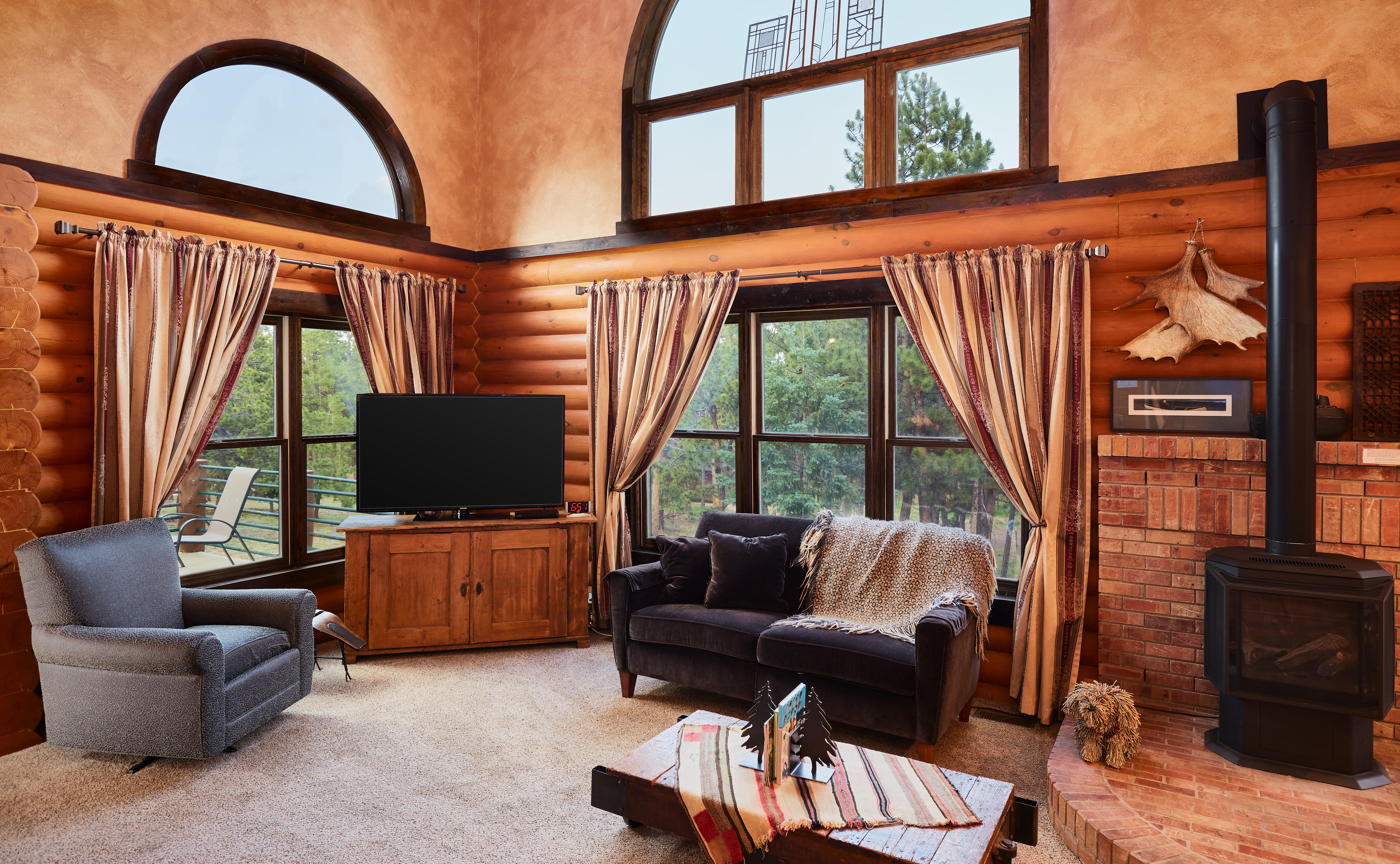 The living room is full of natural light from large windows.