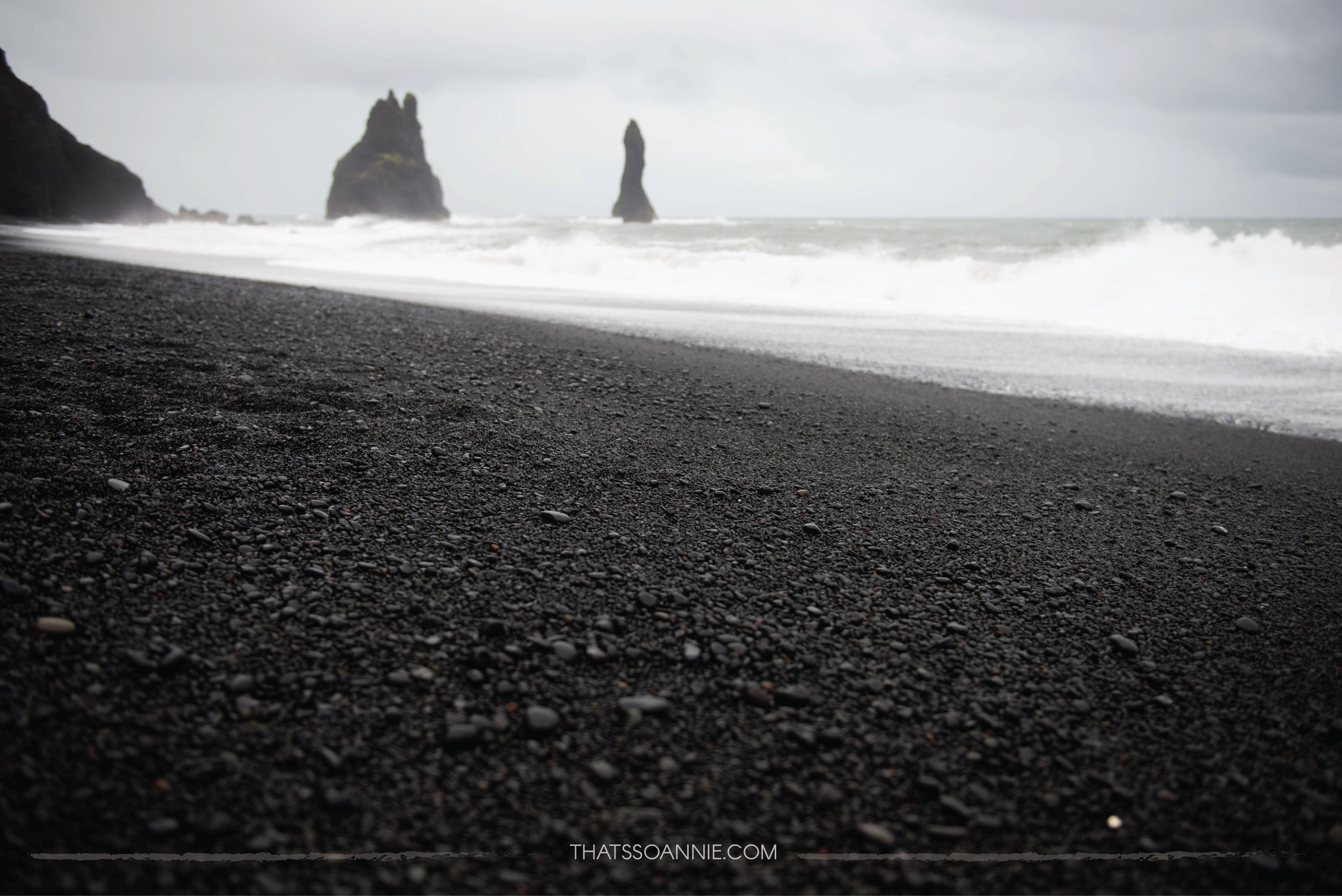 The basalt stacks of Reynisdrangar against the black pebbles of the Reynisfjara beach
