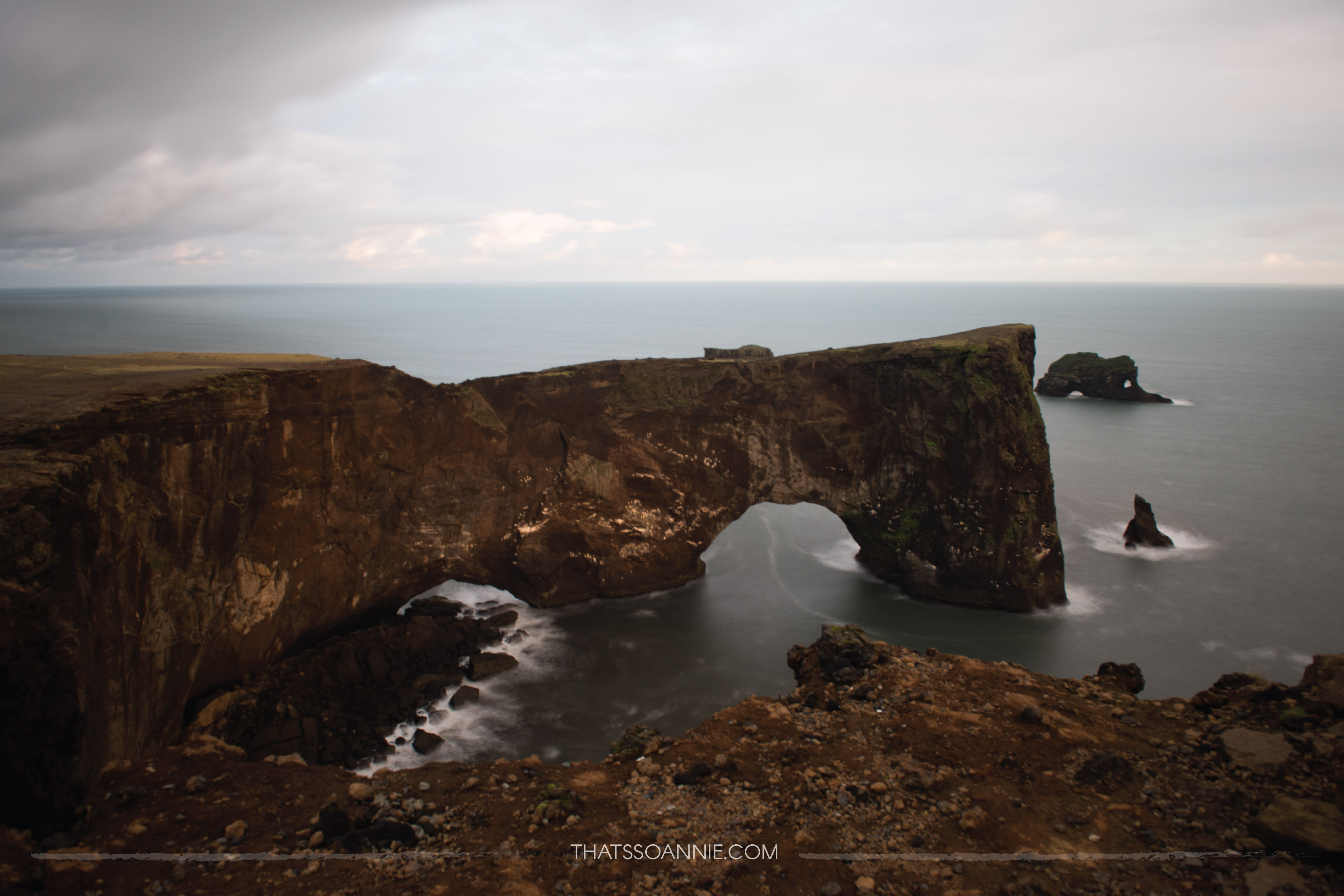 Dyrhólaey's black arch of lava jutting out into the sea.