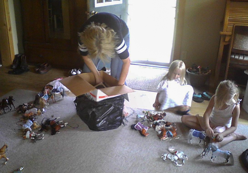 young girls playing with plastic ponies