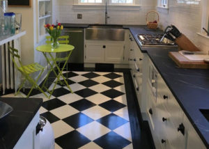 Oiled Vermont Soapstone countertops are the perfect compliment to this stylish black and white kitchen.