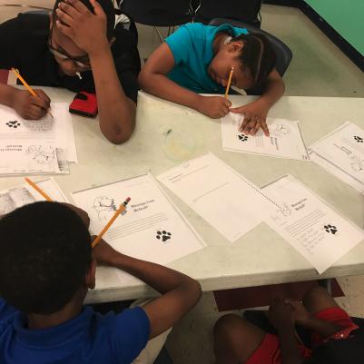 a group of kids completing worksheets together