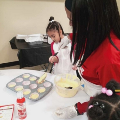an adult helps two little girls with their baking skills